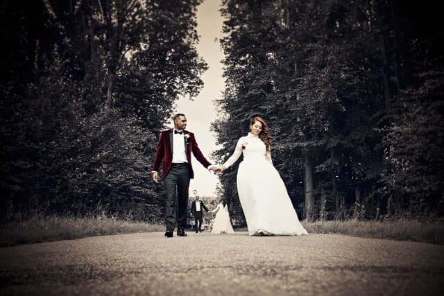 式場へと手を繋ぎ歩む新婚カップル