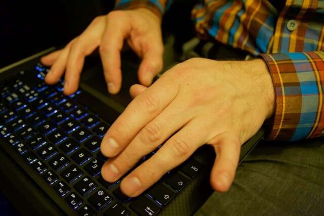 ノートパソコンを使ってSNSを利用する男性
