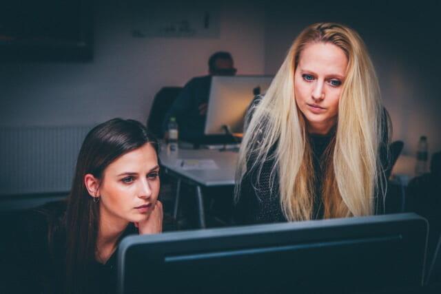 ネット恋愛探し中にパソコンの画面を見ながら悩む2人の女性