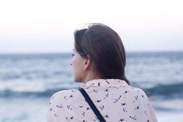海を眺めながらネット恋愛の相手について冷静に考える女の子