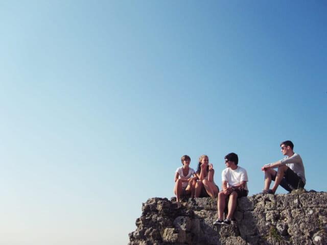 見晴らしの良い丘に座りお互いの距離を保ちながら話をするネットで出会った男女のグループ