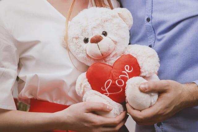 ネットで出会った女性に赤いハートを持ったクマのぬいぐるみをプレゼントする男性