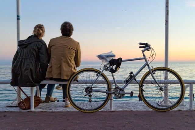 桟橋に座って夕日を眺める幸せそうなネット恋愛カップル