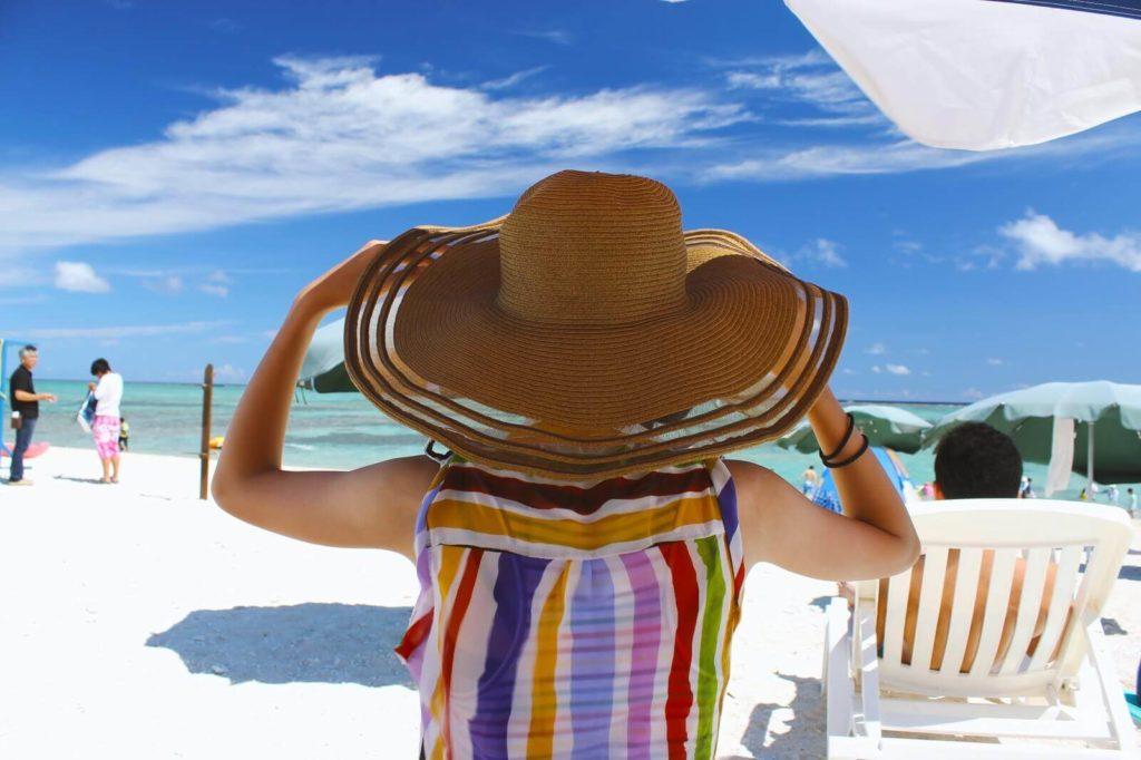 ビーチで大きな麦わら帽子を被る女性
