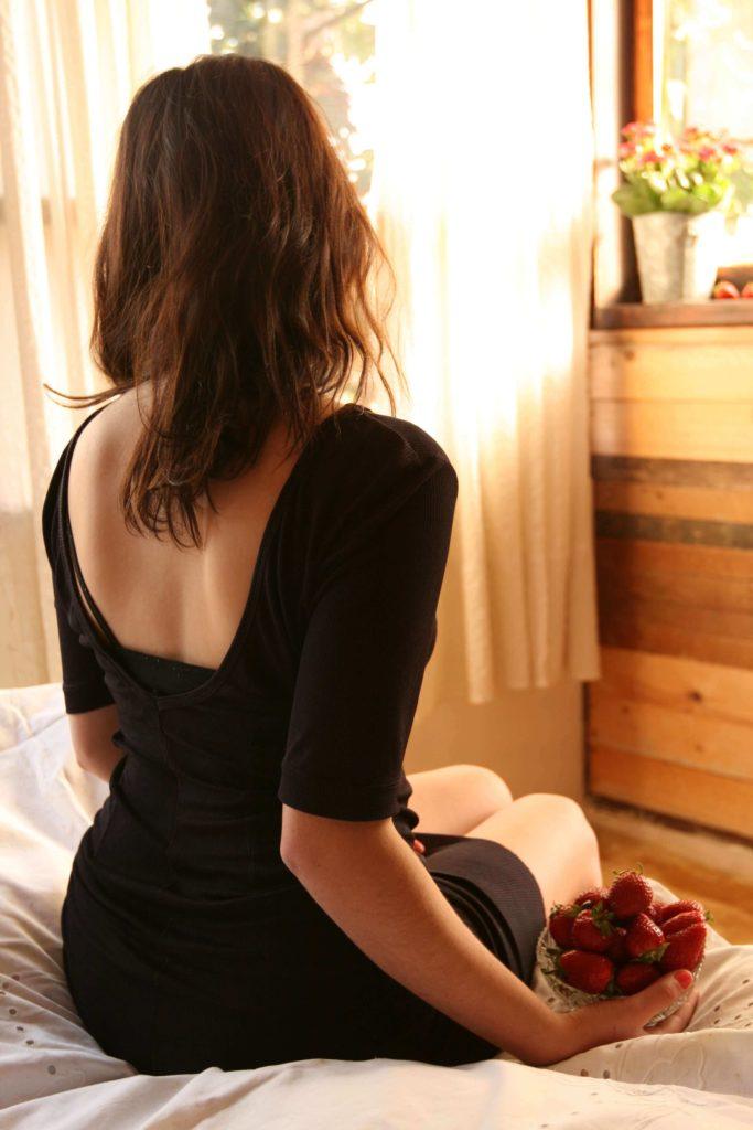 ベッドに座る後姿の女性