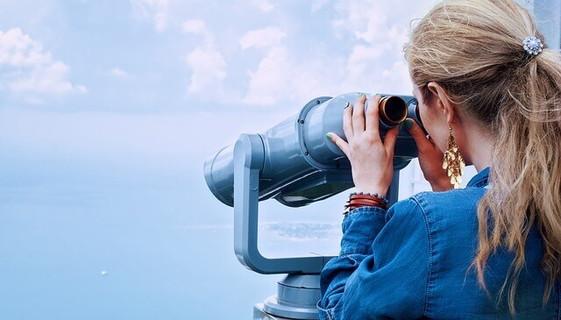 青い海と空が広がる景色を望遠鏡で覗き込むブロンドヘアの女性