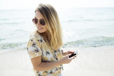 海岸を歩きながらスマホをいじるアロハシャツにサングラス姿の女の子