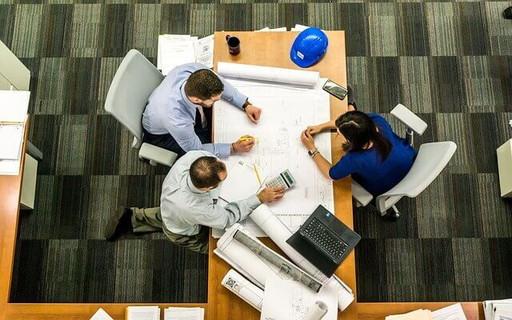デスクの上に図面を広げ話し合う男性2人と女性1人