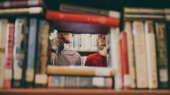 学校の図書室で会話に花を咲かせている男性と女性