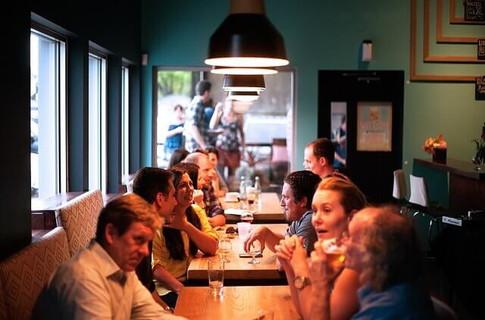 おしゃれなカフェの席につき会話を楽しむ人たち