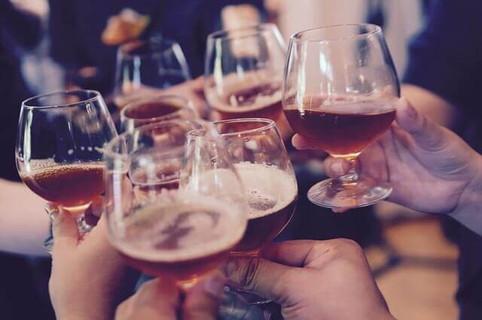 グラスに入ったビールでトーストする仲間たち
