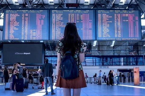 空港の電光掲示板を眺めるリュックを背負った女の子