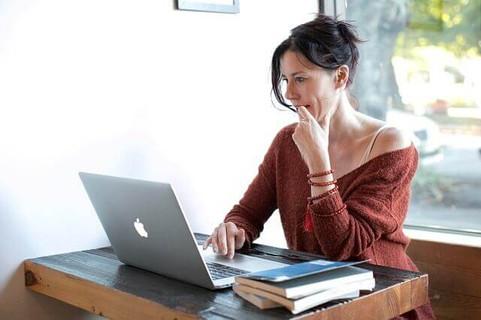 デスクに座りマックブックの画面に夢中になる赤いニットを着た女性