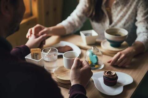 お互いに引き寄せられて手を取り合うカフェのテーブルに向かい合って座った2人