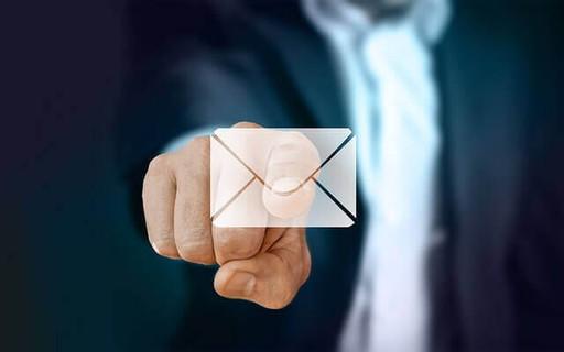 メールのアイコンを人差し指でタッチするスーツ姿の男性