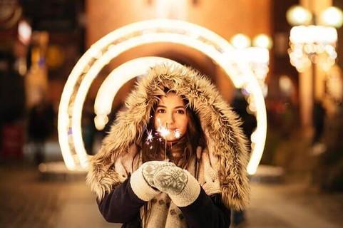 クリスマスのイルミネーションを背景に花火を持つファーの帽子とミトンが暖かそうな女の子