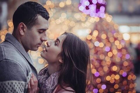 クリスマスツリーの前でキスをする幸せそうなカップル