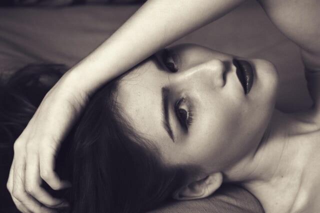 ベッドに寝そべる色気たっぷりのモテるアラサー女性