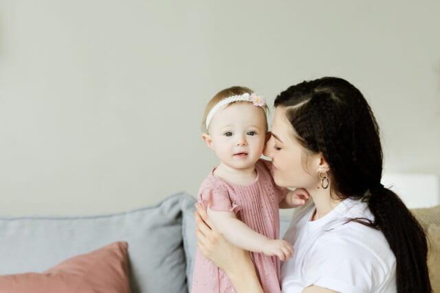笑顔で小さな赤ちゃんの面倒を見るモテるアラサー女性