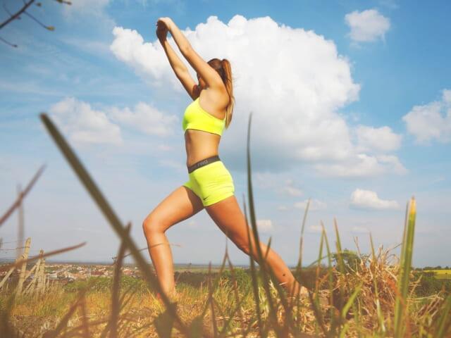 青空の下でランニングウェアを着て伸びをするモテるアラサー女性
