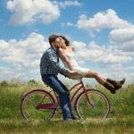 自転車に乗ってキスをするカップル