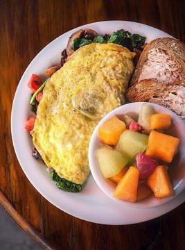 オムレツにトースト、フルーツの朝食