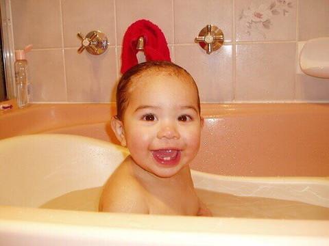笑顔でお風呂に入る赤ちゃん