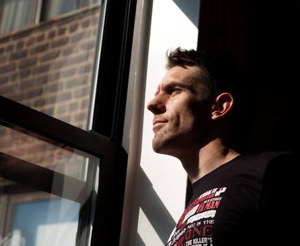 朝日を浴びながら窓の外を見る男性