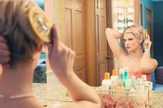 鏡の前でヘアセットをする女性