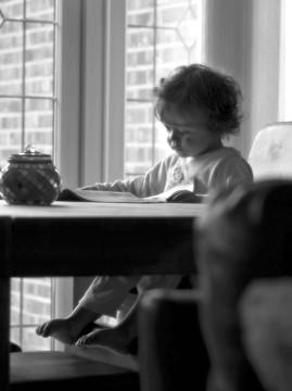 椅子に座って本を読む赤ちゃん