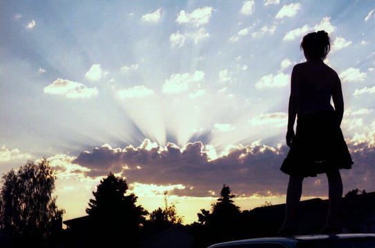 朝日に向かって立つ女性の後ろ姿