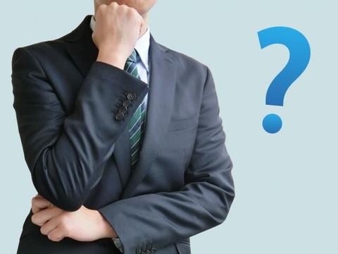 考え事をするグレーのスーツ姿の男性
