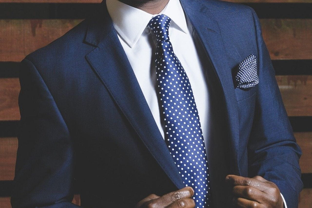 ソファに座ってコーヒーを飲む格好良くスーツを着こなした男性