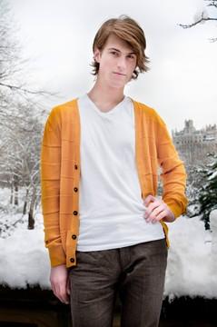 白いTシャツに黄色いカーディガンを羽織ってポーズを決める男性