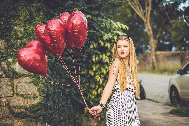 白いタンクトップ姿で赤いダリアを銜える金髪の女性