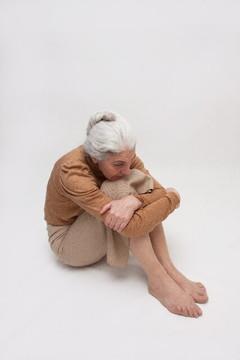 膝を抱えて座り込む老婦人