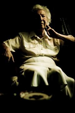 薄暗い部屋でソファに座る老婦人