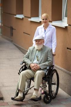 白髭をたくわえ車椅子に乗る老紳士と白衣の女性