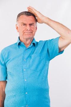 困り顔で頭をかく青い半そでシャツの男性