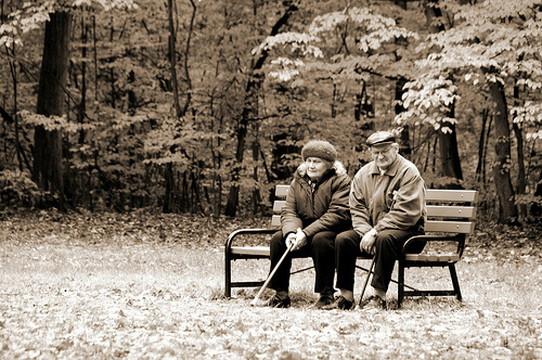 ベンチに座り考えごとをする老夫婦