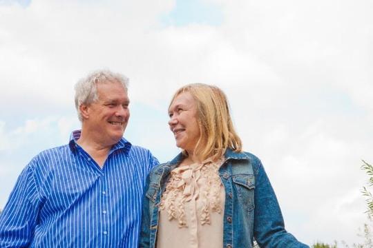 青空のした笑顔で見つめ合う老夫婦