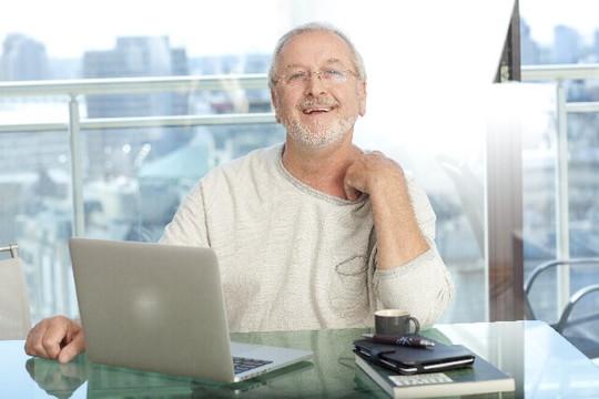 ノートパソコンを前に微笑む老紳士