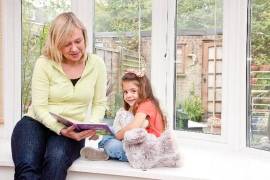 くまのぬぐるみを持った少女に絵本を読む老婦人