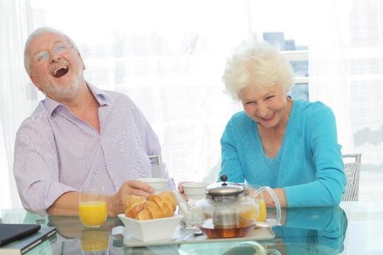 食事をしながら語らう笑顔の老夫婦