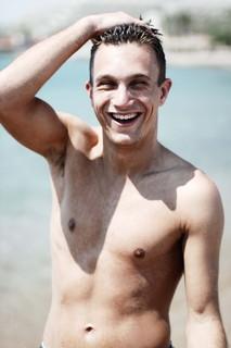 満面の笑顔で海から上がる男性