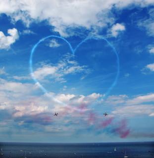 空に大きく飛行機雲で描かれたハート