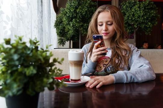 ミルクたっぷりのアイスカフェラテを前にしてスマートフォンを覗き微笑むロングヘアの女性