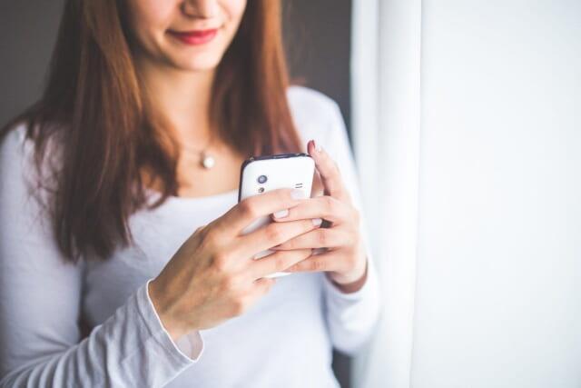 食事をしながら笑顔でスマートフォンを眺める女性