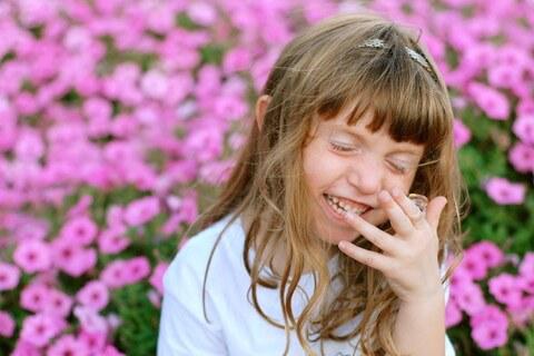 ピンク色の花が咲くお花畑でおもちゃの指輪をつけて微笑む少女