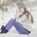 雪の中に座り込むデニムにセーターを着た女性